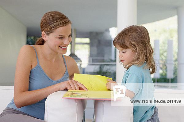 Mutter hilft ihrer Tochter beim Lesen