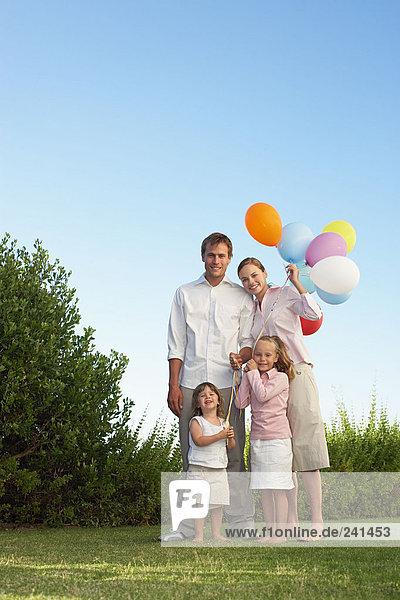 Porträt der Familie stand im Garten mit Luftballons