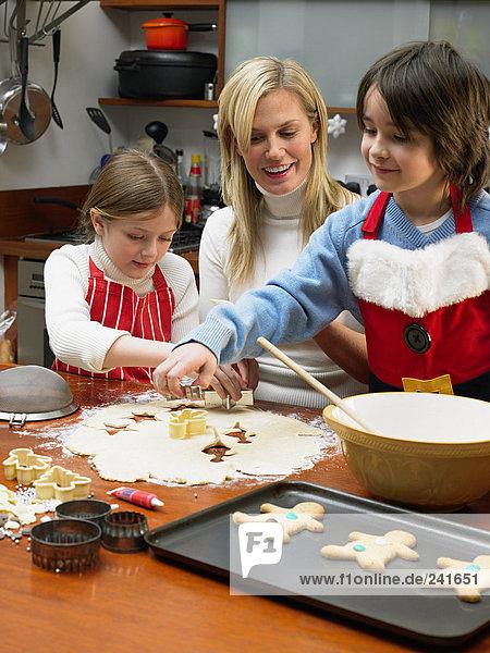 Mutter und Kinder machen Kekse