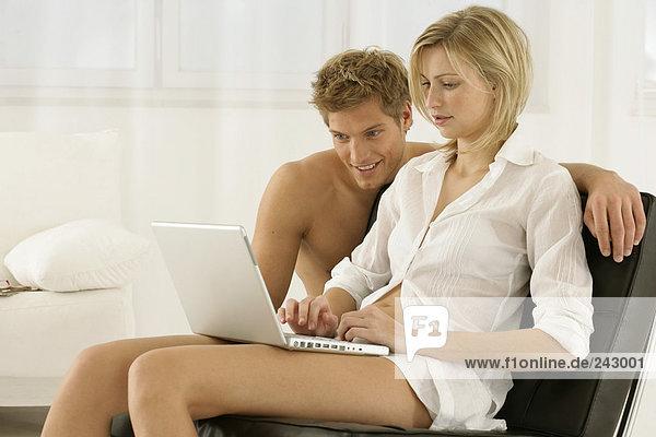 Junges blondes Paar bedient ein Laptop - Partnerschaft,  fully_released