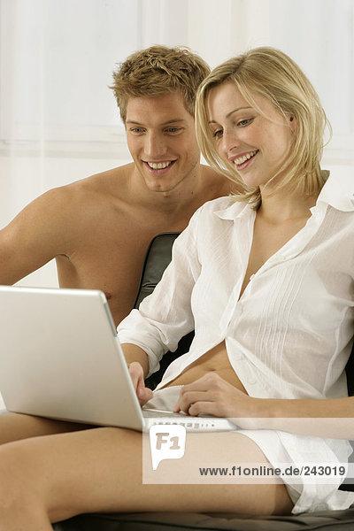 Junges leichtbekleidetes Paar mit blonden Haaren sitzt am Laptop - Partnerschaft  fully_released