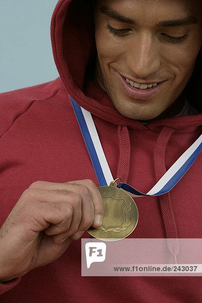 Lächelnder Sportler hält seine Goldmedaille in der Hand  fully_released