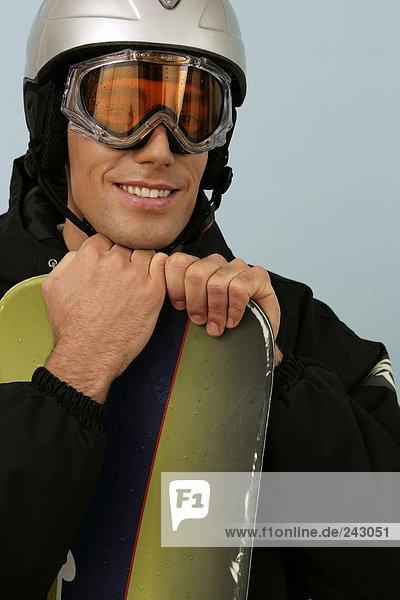 Ein Snowboarder mit Skibrille und Schutzhelm stützt sich auf sein Brett  fully_released