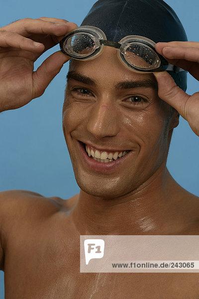Porträt von einem lächelndem Schwimmer mit Badekappe und Schwimmbrille  fully_released Schwimmkappe und Schwimmbrille