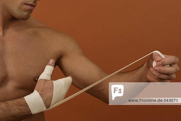 Ein Mann bandagiert seine Hand  fully_released