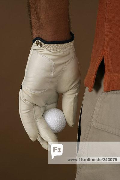 Ein Golfspieler hält einen Ball in der Hand  fully_released