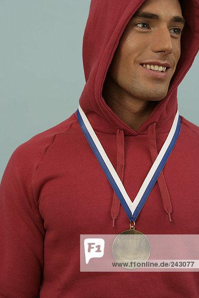 Ein Sportler trägt eine Medaille  um dem Hals  fully_released