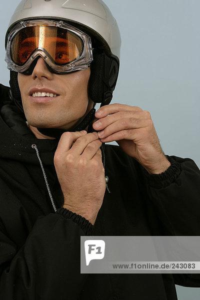 Ein Mann mit Skibrille schließt den Verschluss von seinem Schutzhelm  fully_released