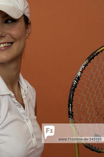 Lächelnde Tennisspielerin mit einem Tennisschläger  fully_released