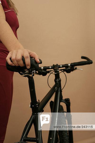 Mountainbikerin hält ihr Mountainbike fest  fully_released