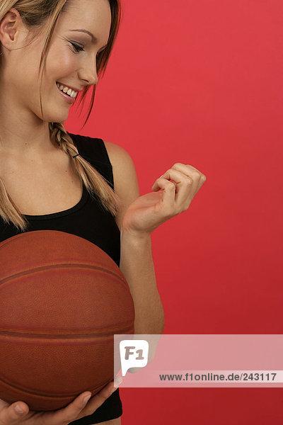 Junge Frau hält einen Basketball in der Hand und betrachtet ihre Nägel  fully_released