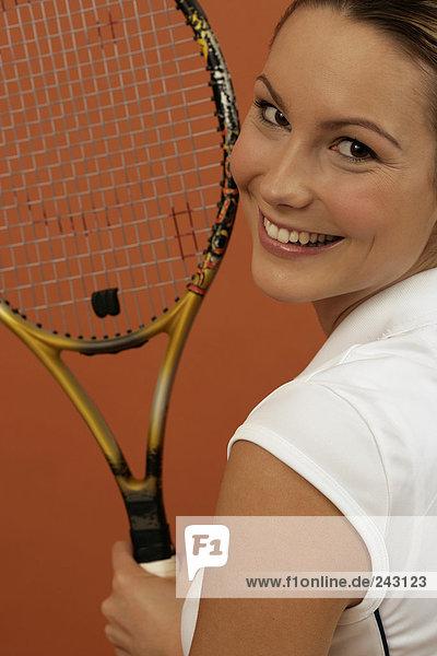 Tennisspielerin mit einem Schläger lächelt in die Kamera  fully_released