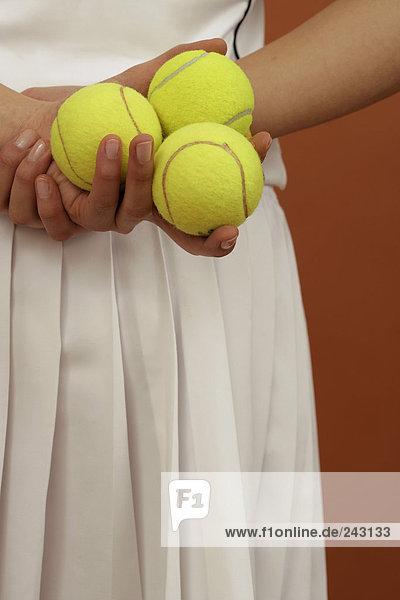 Tennisspielerin hält Bälle in der Hand  fully_released