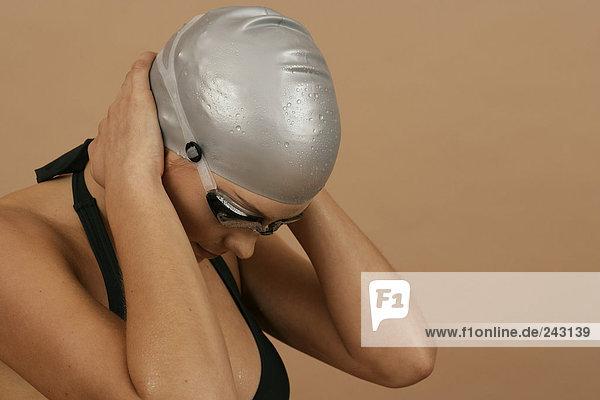 Schwimmerin mit Badekappe und Schwimmbrille hält sich die Ohren zu  fully_released Schwimmkappe und Schwimmbrille
