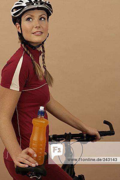 Mountainbikerin auf einem Mountainbike hält eine Flasche in der Hand  fully_released