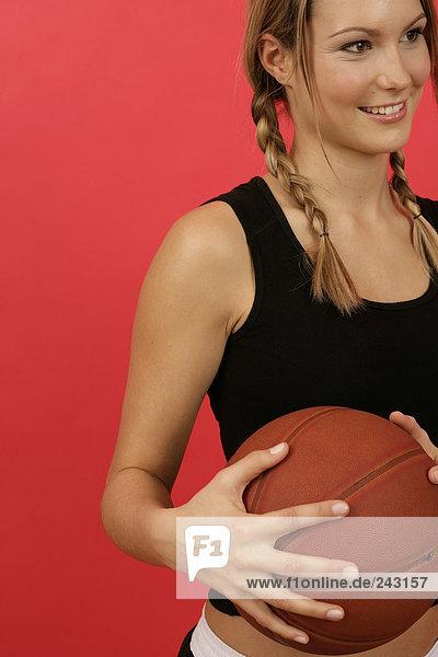 Junge Frau hält einen Basketball fest  fully_released