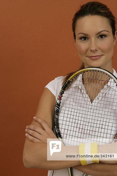Tennisspielerin hält einen Tennisschläger im Arm und blickt in die Kamera  fully_released