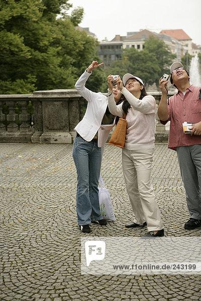 Drei Asiaten mit Fotoapparaten stehen auf einem Platz und sehen nach oben - Tourismus  fully_released
