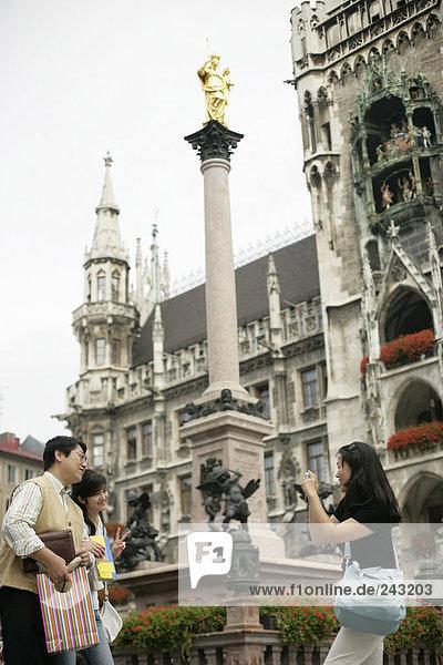 Junge Asiatin fotografiert ihre Eltern unter einer goldenen Marienstatue - Städtereise - Tourismus  fully_released