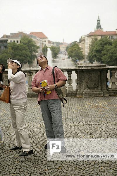 Drei Asiaten mit Fotoapparaten stehen auf einem Platz und sehen nach oben - Tourismus,  fully_released