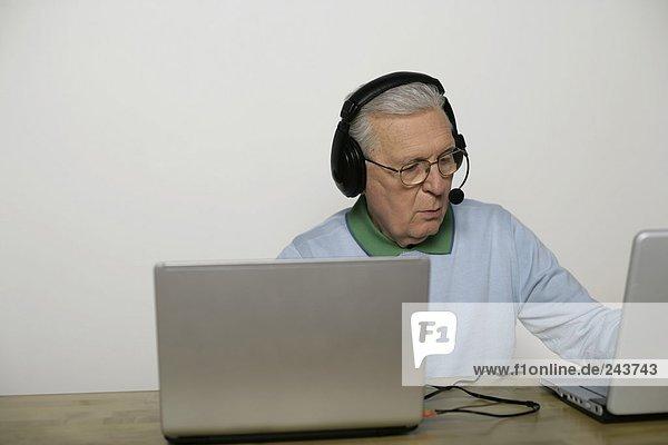 Alter Mann mit Headset sitzt vor zwei Laptops  fully_released