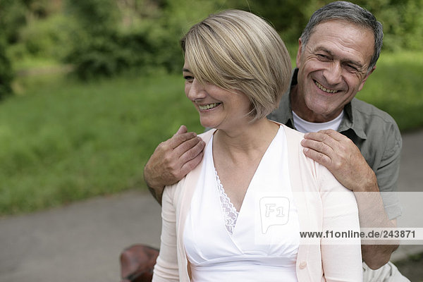 Älterer Mann umarmt Frau von hinten  beide lächeln  fully_released