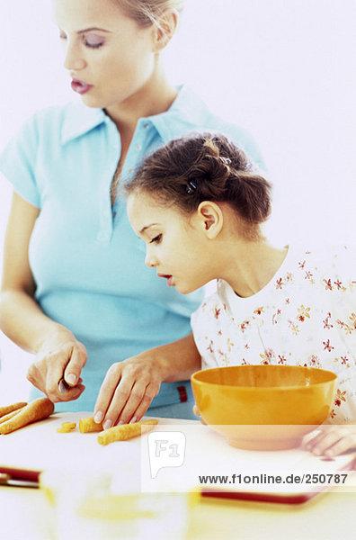 Tochter sieht zu  wie Mutter Karotte schneidet.