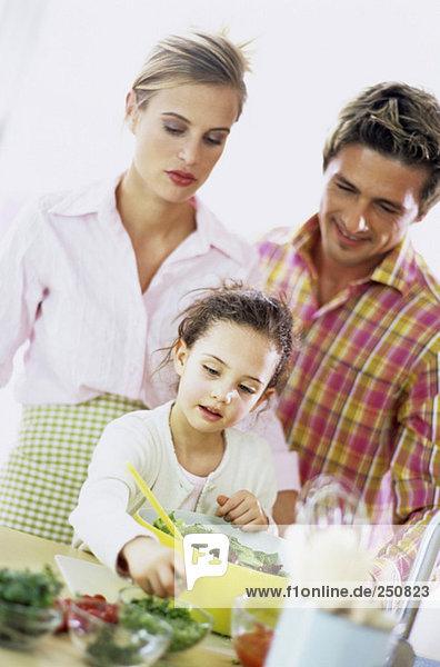Eltern beobachten Tochter (6-7) bei der Zubereitung von Salat