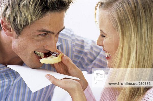 Frau füttert Mann Kuchen mit Marmelade,  Nahaufnahme