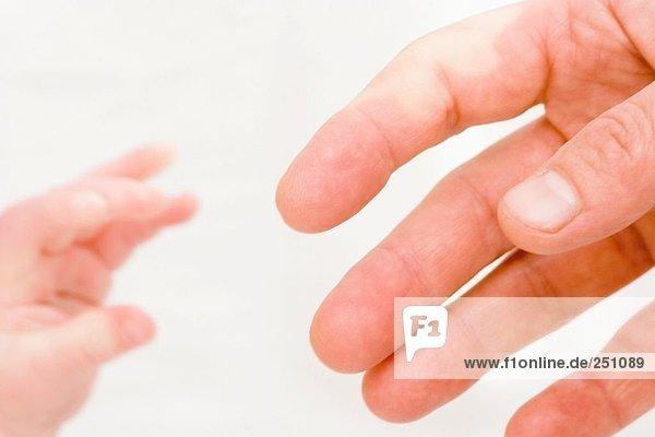 Nahaufnahme der Hände des Mannes und baby