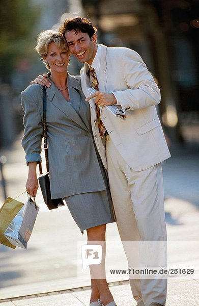 10317726  outside  laugh  middle age  old person  pair  couple  Shoping  town  city  stand  pockets  bags