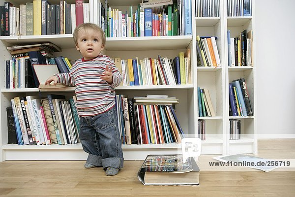 Junge steht vor einem Bücherregal  fully_released