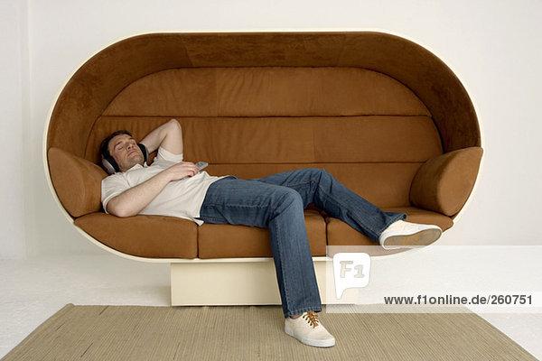 Mann entspannt auf dem Sofa mit Kopfhörer und Fernbedienung