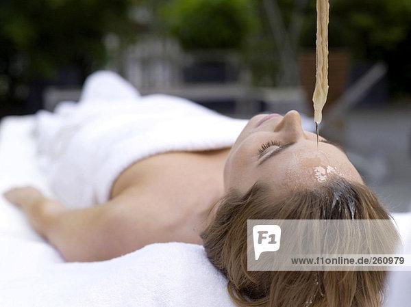 Junge Frau im Spa liegend mit Öl auf die Stirn gegossen  Augen geschlossen