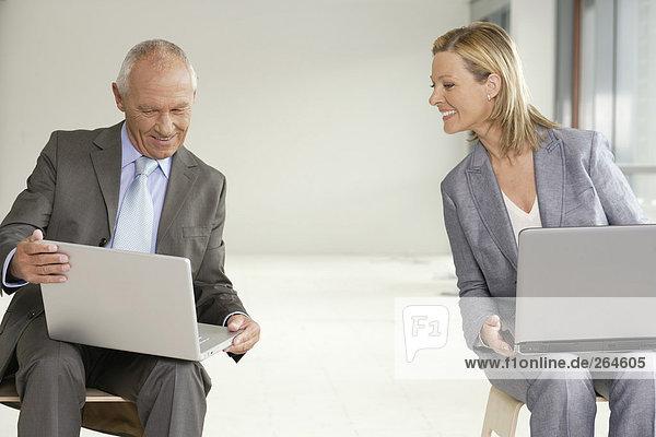 Manager und Geschäftsfrau mit Laptops auf dem Schoß  fully_released