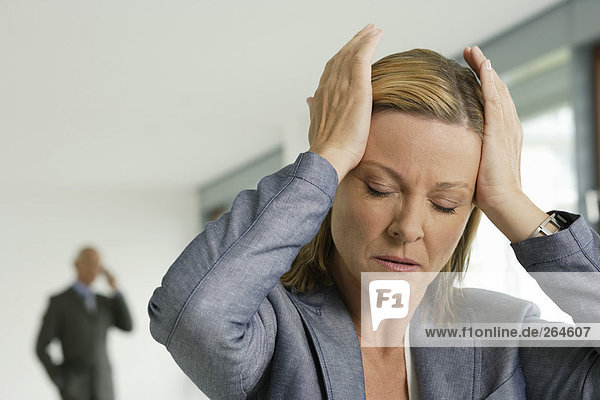 Geschäftsfrau fasst sich gestresst an den Kopf  Person im Hintergrund  fully_released