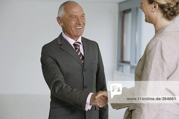 Manager und Geschäftsfrau gut gelaunt beim Händeschütteln  fully_released