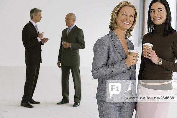 Gruppe von Geschäftsleuten in einem leeren Büro trinkt aus Kaffeebechern  fully_released