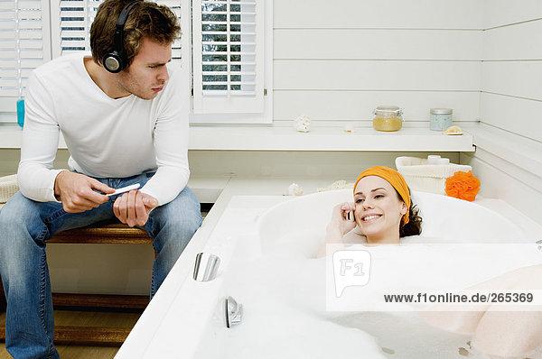 Frau  die im Bad anruft  Mann  der seine Nägel feilt.