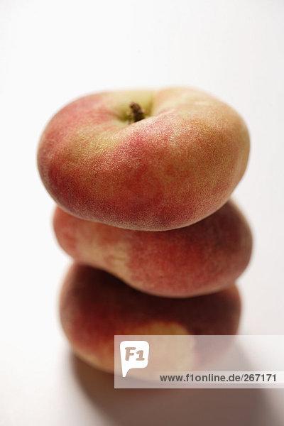 Drei flache Pfirsiche  gestapelt