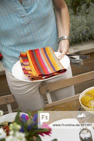 Frau deckt Tisch für sommerliche Grillparty
