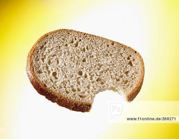 Angebissene Brotscheibe vor gelbem Hintergrund