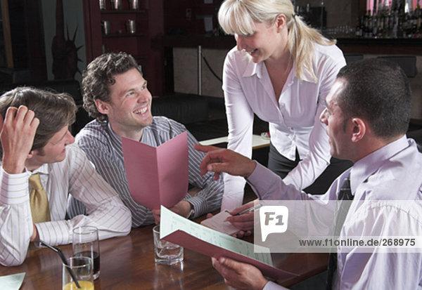 junge Kellnerin die Bestellungen aus drei Gäste im restaurant