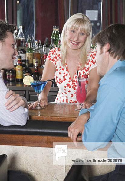 blond Barmaid serving Cocktails für zwei Geschäftsleute