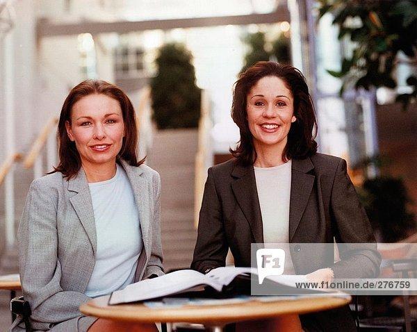 Porträt von zwei Geschäftsfrauen an einem Tisch.