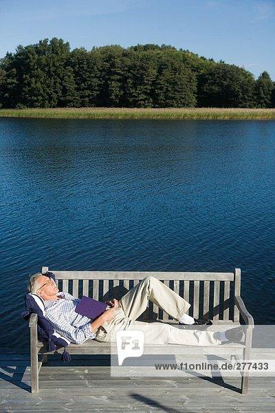 Ein Mann schläft auf einer Bank.