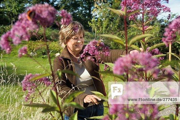 Eine Frau mit Blumen in einem Garten aufhielt.