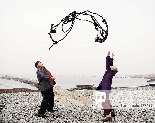 Ein Mann und eine Frau werfen ein Seil an einem Strand.
