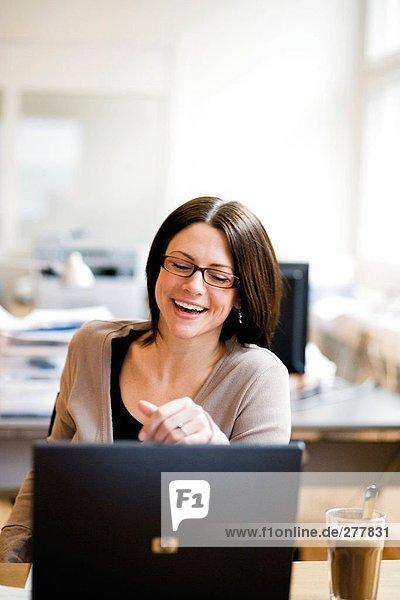 Eine lachend Frau an ihrem Arbeitsplatz.