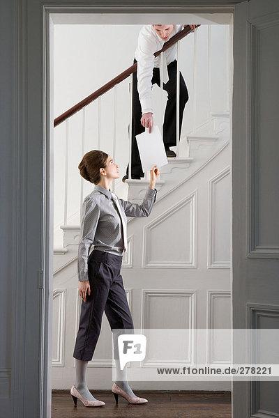 Frau übergibt Papier an Mann